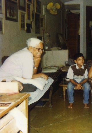 Bhupen watching a sports match on television with Deepak, Pandu's son.