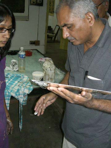 Vijay Bagodi checking a plate with a student at MS University